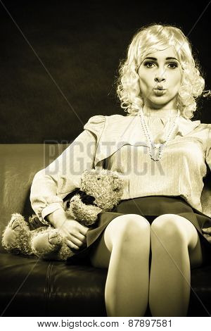 Childlike Woman And Teddy Bear Sitting On Couch
