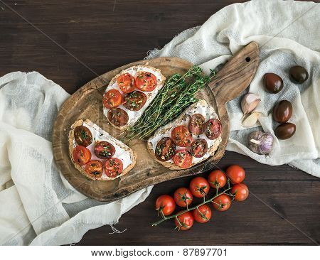 Sandwiches brushtta with roasted cherry tomatoes, soft cheese,