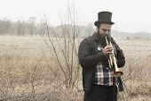 stock photo of gypsy  - Stylish bearded gypsy plays trumpet on a wilderness path