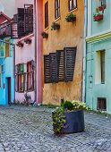 stock photo of cobblestone  - Old cobblestone street with flower decorated colourful buildings in Sighisoara - JPG