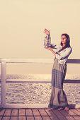 stock photo of kerosene lamp  - Full length young woman on pier with oil kerosene lamp - JPG