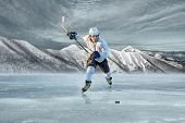 stock photo of ice hockey goal  - Ice hockey player on the ice in mountains - JPG
