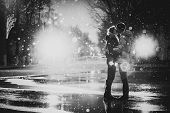 stock photo of couples  - In love couple kissing in the snow at night city street black and white - JPG