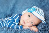 pic of knitted cap  - cute newborn baby in knitted cap on a blue background - JPG