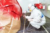 picture of paint spray  - auto repair worker painting a red car in a paint chamber during repair work - JPG