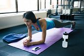 foto of yoga mat  - Young woman doing yoga exercises on yoga mat at gym - JPG