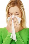 stock photo of sneezing  - Ill woman sneezing to tissue - JPG
