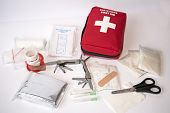 "pic of bandage  - Open first aid kit with bandages scissors ""triangle scarf"" syringe plaster knife tools gauze etc
