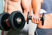 stock photo of fitness man body  - Couple exercising with dumbbells in a gym - JPG
