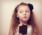 Постер, плакат: Thinking Humor Kid Face Eating Chocolate Closeup Vintage