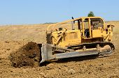 picture of bulldozer  - Large bulldozer moving rock and soil for a fill lift at a new commercial development road construction project - JPG