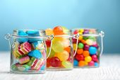 stock photo of jar jelly  - Colorful candies in jars on table on blue background background - JPG