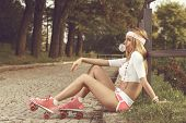 image of roller-skating  - Sexy woman with roller skates chewing gum - JPG