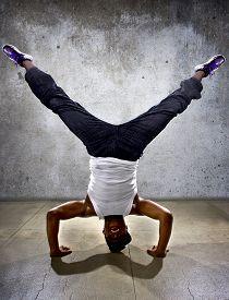 foto of inverted  - Inverted black breakdancer doing a headstand or handstand or urban yoga - JPG