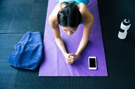 stock photo of yoga mat  - Top view portrait of a young woman doing yoga exercises on yoga mat at gym - JPG