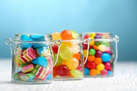 picture of jar jelly  - Colorful candies in jars on table on blue background background - JPG