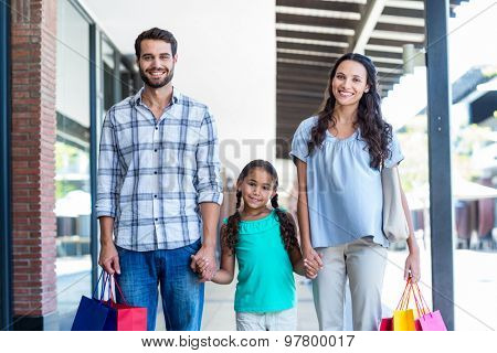 Portrait of a happy family with shopping bags on a sunny day