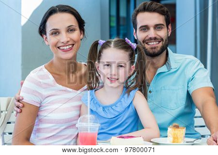 Portrait of a family eating at the restaurant on a sunny day
