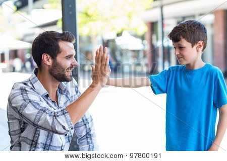 Son and father doing high five at the mall