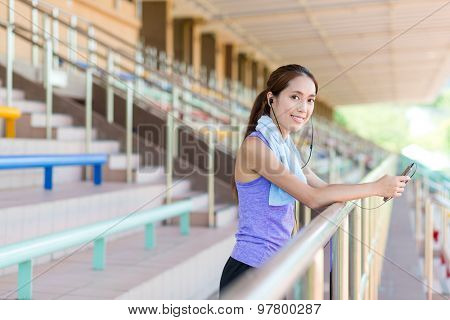 Sporty Woman listen to music and stand on the audience part of the stadium