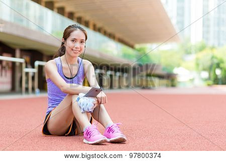 Sporty Woman listen to music ans sitting on sport arena