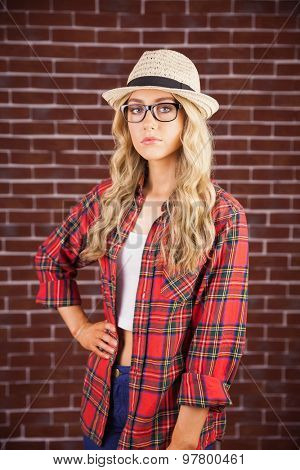 Portrait of gorgeous blonde hipster with hand on hips against red brick background