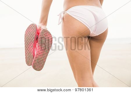 Fit woman in bikini holding flip flops at the beach