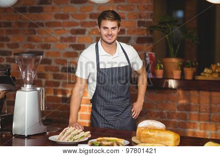Portrait of a waiter bended over a food table at the coffee shop