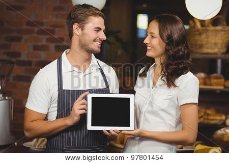 Smiling co-workers showing a tablet at the coffee shop