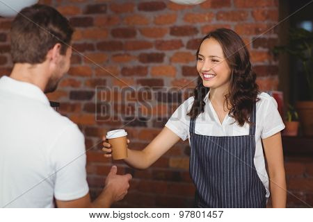 Pretty smiling barista serving a customer at the coffee shop