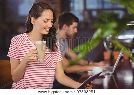 Smiling young woman enjoying latte and using tablet computer at coffee shop