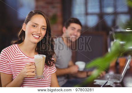 Portrait of smiling young woman with latte in front of her friend at coffee shop