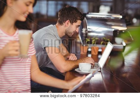 Smiling young man sitting at bar and using laptop in a cafe