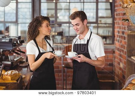 Smiling waiter and waitress holding cup of coffee at coffee shop