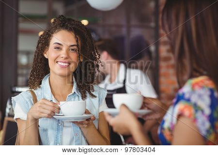 Portrait of smiling pretty customer holding cup of coffee in front of barista at coffee shop
