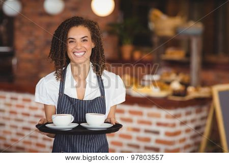 Portrait of barista holding a tray of coffee cups at the coffee shop
