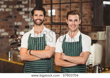 Portrait of two smiling baristas with arms crossed at the coffee shop