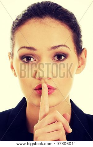 Businesswoman making silent sign with finger on lips.