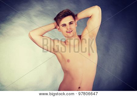 Young shirtless muscular man smiling to camera.