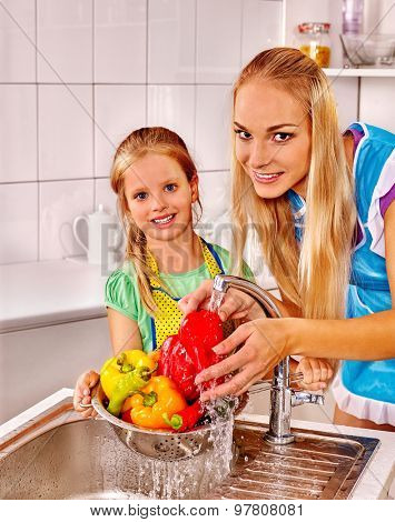 Happy family with little daughter washing fruit under water at kitchen.
