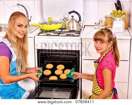 Mother and daughter bake cookies in oven . Kitchen.