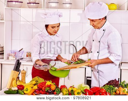 Happy man and young woman professional in chef hat cooking chicken together.