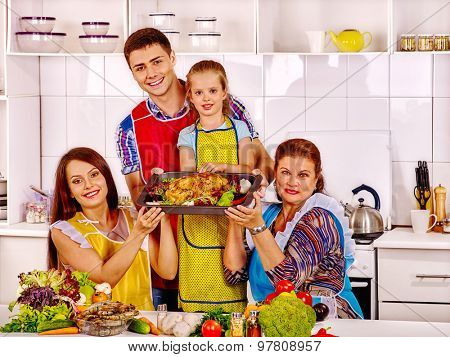 Happy family with grandmother and child  at kitchen. Cooking chicken.