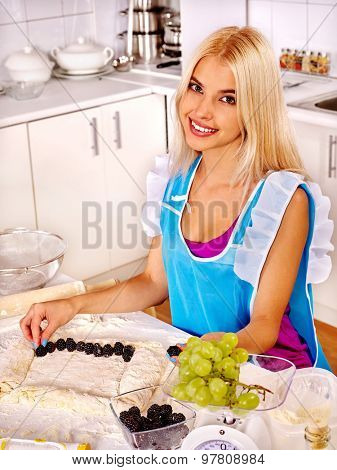 Young happy blond woman  baking cookies in oven.