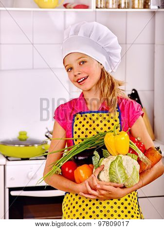 Child girl in hat holding vegetable at kitchen.