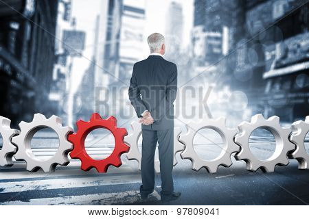 Rear view of mature businessman posing against blurry new york street