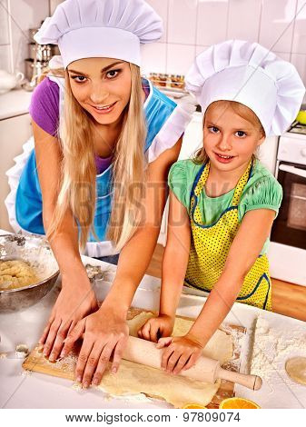Mother and happy daughter baking cookies.