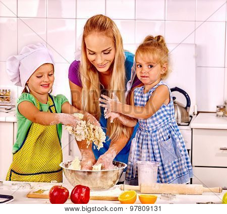 Mother and two daughter baking cookies.