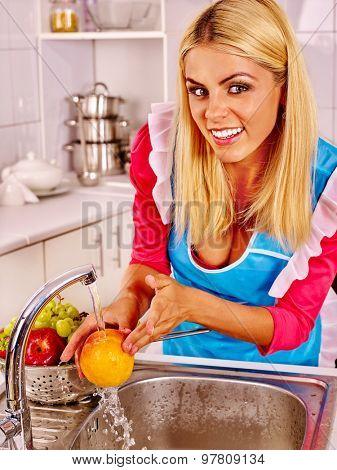 Happy woman washing peach fruit at kitchen.