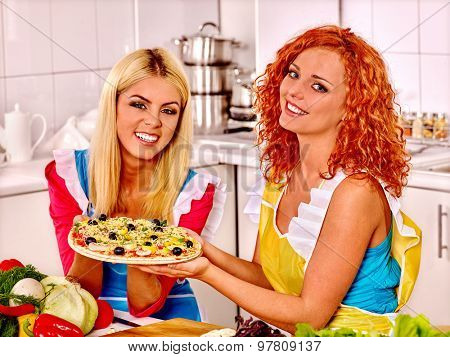 Two happy women friend cooking pizza at kitchen.